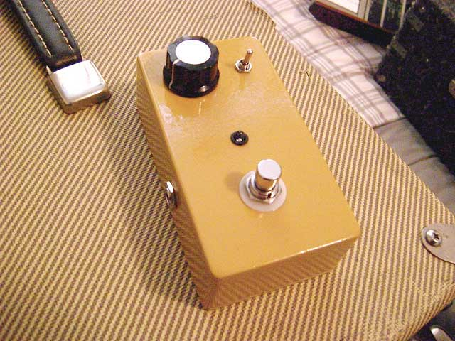 A guitar pedal with one knob sits on top of an amp.