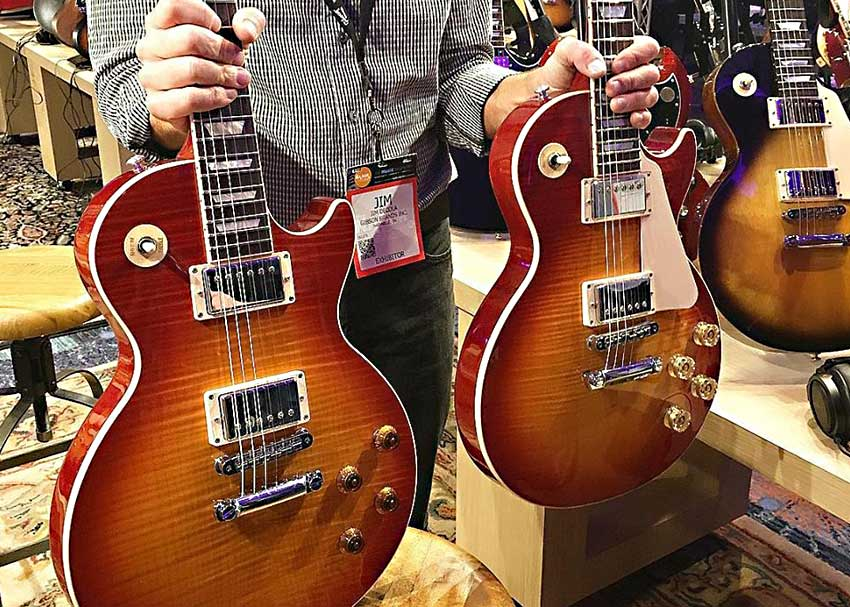Gibson Head Luthier Jim DeCola holds up both a Traditional and High Performance 2016 Les Paul Standard at NAMM 2016.