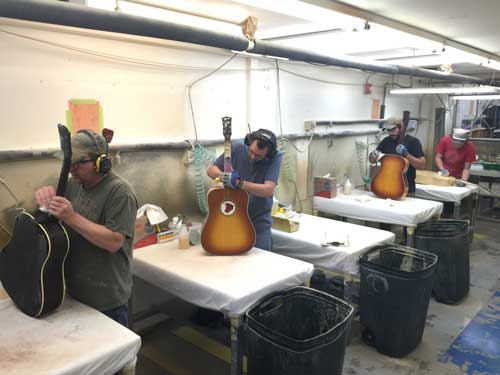 Gibson factory workers adding some final touches before the bridges are attached.
