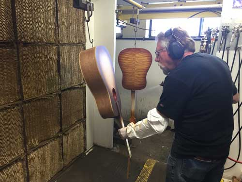 Spraying the sunburst finish by hand before the nitrocellulose lacquer is applied.