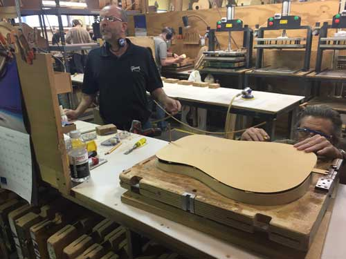 A Gibson factory worker making sure that the top aligns just right with the rest of the body.