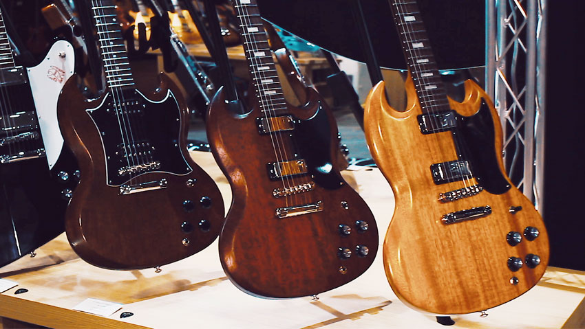 """The two SG models in the center and right are SG Classics, this year sporting rocking mini humbuckers for a distinctively vintage growl and look. On the left is a SG Faded, which is finished with a retro nitro gloss for an elegantly aged appearance, full-sized humbuckers and a larger """"batwing"""" pickguard."""