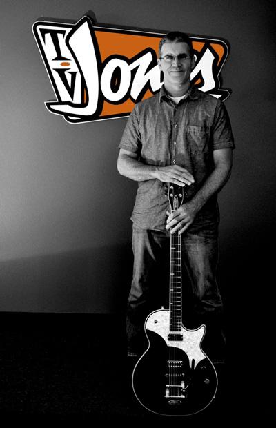 Tom Jones poses with a TV Jones Guitar