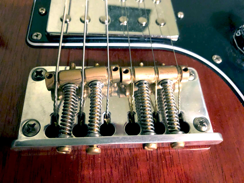 Bridges with barrel saddles, like the PRS Plate-style bridge shown here, may require a hint of compromise.